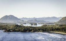 Возвышенный вид на прибрежный пейзаж с горами и зелеными деревьями — стоковое фото