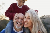 Grandparents with grandson on shoulders looking at camera smiling — Stock Photo