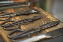 Close-up de glassblowers mão ferramentas colocadas em uma linha na superfície de madeira gasto — Fotografia de Stock