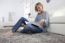 Mid adult woman sitting on rug reading book — Stock Photo