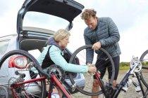 Велосипедисти підготовка велосипед для їзди біля автомобіля — стокове фото