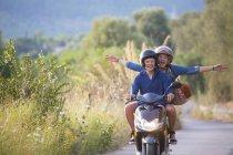 Jeune femme chevauchant un pillion en cyclomoteur les bras ouverts sur une route rurale, Majorque, Espagne — Photo de stock