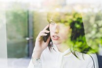 Vue fenêtre de la jeune femme d'affaires parlant sur smartphone — Photo de stock