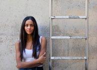 Frau lehnt an Betonwand neben Leiter, Arme verschränkt und blickt in Kamera — Stockfoto