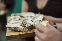 Close up of customer eating fresh oysters at cooperative food market stall — Stock Photo