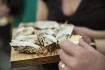 Близько від клієнта, їдять свіжі устриці на ринку кооперативного харчова ларьок — стокове фото