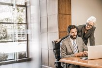 Businesspeople at desk looking at laptop smiling — Stock Photo