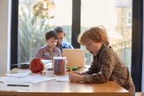 Ragazzo colorazione a tavolo da pranzo mentre papà utilizzando computer portatile con fratello — Foto stock