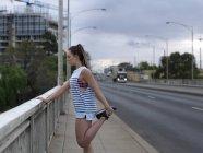 Jeune coureur féminin qui s'étend de jambes sur le pont de la route à l'aube — Photo de stock