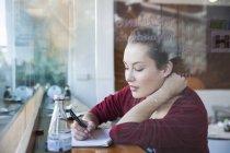 Mujer joven sentada en la cafetería, escribiendo en el Bloc de notas - foto de stock
