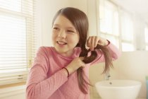 Girl plaiting long brown hair in bathroom — Stock Photo