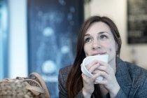 Jovem mulher bebendo café no café olhando para cima — Fotografia de Stock