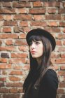Young woman in front of brick wall — Stock Photo