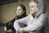 Two female runner friends sitting on warehouse platform — Stock Photo