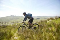 Cyclist cycling on hillside — Stock Photo