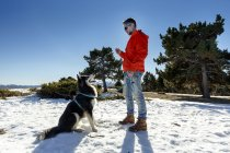 Mature man training dog in snow covered landscape — Stock Photo