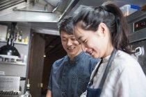 Азіатські кухарі в комерційній кухні посміхаючись — стокове фото