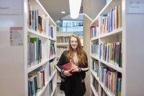 Junge Universitätsstudentin, die in der Bibliothek arbeitet — Stockfoto