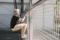 Молода людина скелелазіння колючого дроту — стокове фото