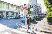 Jeune femme se promenant à travers la ville passage pour piétons — Photo de stock