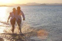 Пара прогулок в морской воде с брызгами, закат на заднем плане — стоковое фото