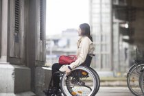 Young woman using wheelchair waiting for city elevator — Stock Photo
