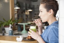 Young woman sitting at bar in cafe, drinking drink through straw — Stock Photo