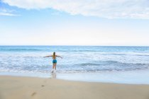 Rear view of young woman running into sea, Dominican Republic, The Caribbean — Stock Photo