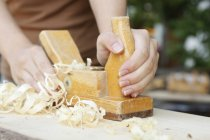 Cropped view of woman using wood plane — Stock Photo