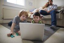 Frères jouant jeu d'ordinateur portable sur tapis de chambre, parents sur canapé — Photo de stock