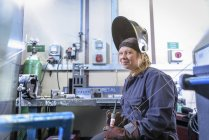 Female apprentice welder holding equipment in car factory, portrait — Stock Photo