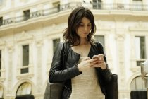 Woman reading smartphone text in Galleria Vittorio Emanuele II, Milan, Italy — Stock Photo