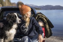 Young woman and dog looking out from pick up on lakeside in Bavarian Alps — Stock Photo