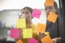 Two businesswomen drinking coffee and staring at sticky notes on office glass wall — Stock Photo