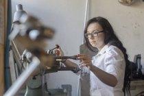 Woman in bicycle repair shop repairing bicycle part — Stock Photo
