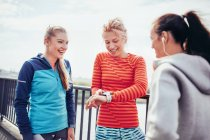 Drei Läuferinnen koordinieren Zeit auf Stadtsteg — Stockfoto