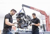 Инженеры, работающие над двигателями на заводе гоночных автомобилей — стоковое фото