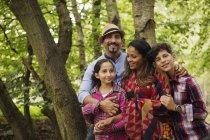 Retrato de la familia de pie en el bosque, sonriendo - foto de stock