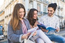 Three friends, sitting outdoors, looking at magazines, Lisbon, Portugal — Stock Photo