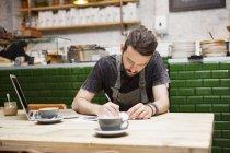 Junge männliche Café-Besitzerin erledigt Papierkram am Tisch — Stockfoto