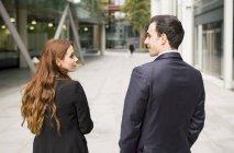 Vista posterior de empresarios en ciudad cara a cara sonriente - foto de stock