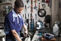 Young man using pliers in repair workshop — Stock Photo