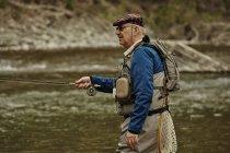 Mature man fishing in river — Stock Photo