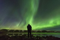Silhouette of man photographing Northern Lights, Kleifarvatn, Iceland — Stock Photo