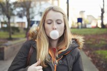 Portrait of young woman, outdoors, blowing bubble with bubblegum — Stock Photo