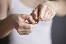 Cropped close up of young woman removing medicine capsule from blister pack — Stock Photo