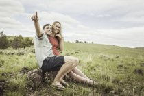 Jeune couple pointant de flanc de coteau, Cody, Wyoming, Usa — Photo de stock