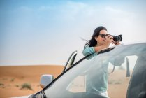 Female tourist photographing from off road vehicle in desert, Dubai, United Arab Emirates — Stock Photo