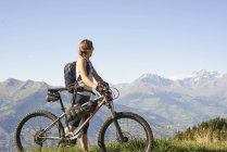 Female mountain biker looking out at mountain landscape, Aosta Valley, Aosta, Italy — Stock Photo