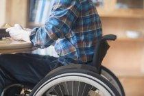 Joven con silla de ruedas conectando el panel de control y el transformador en la mesa de la cocina - foto de stock